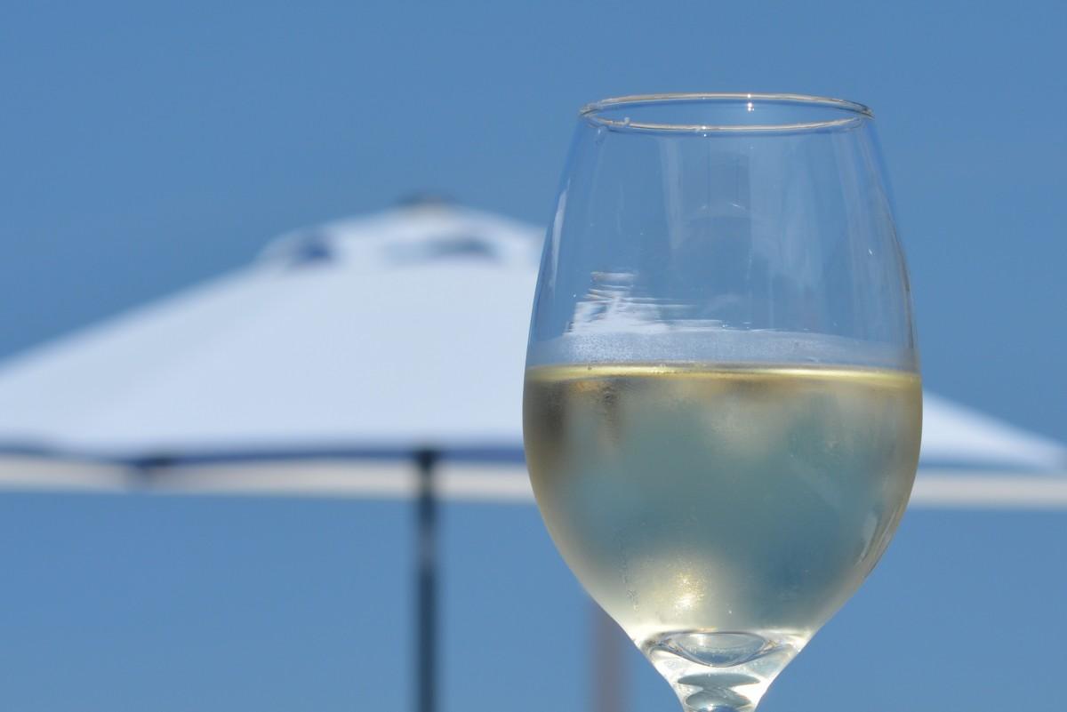 verre de vin blanc sur fond de ciel blanc et de parasol